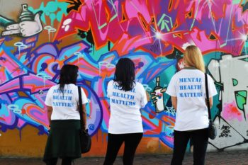 Women with Mental Health Matters tea shirts looking at a wall with graffiti on it