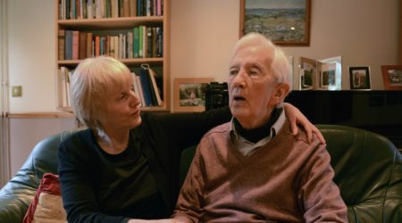 Older woman comforts elderly man