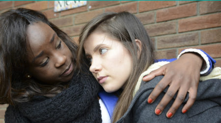 A young woman is consoled by her friend