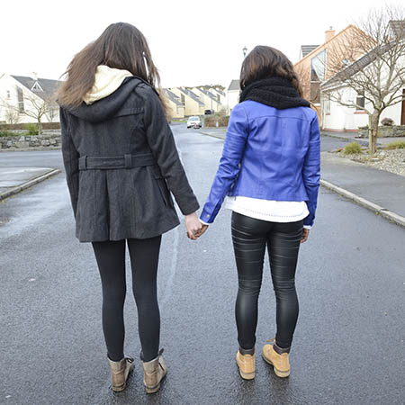 A young woman suffering from depression has her hand held in support by a friend