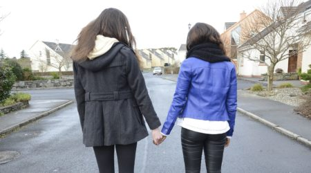 Two young women holding hands for support