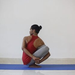 Young man sitting on exercise mat doing yoga