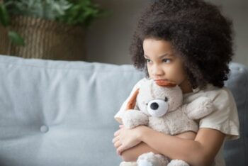 Photo of young girl holding a teddy bear tight