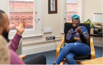 Living Well Uk - laughing and smiling woman sat in chair during a therapy session
