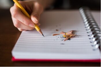 Child's hand writing on a notebook with pencil shavings on the page