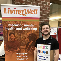 Man standing beside Living Well UK sign